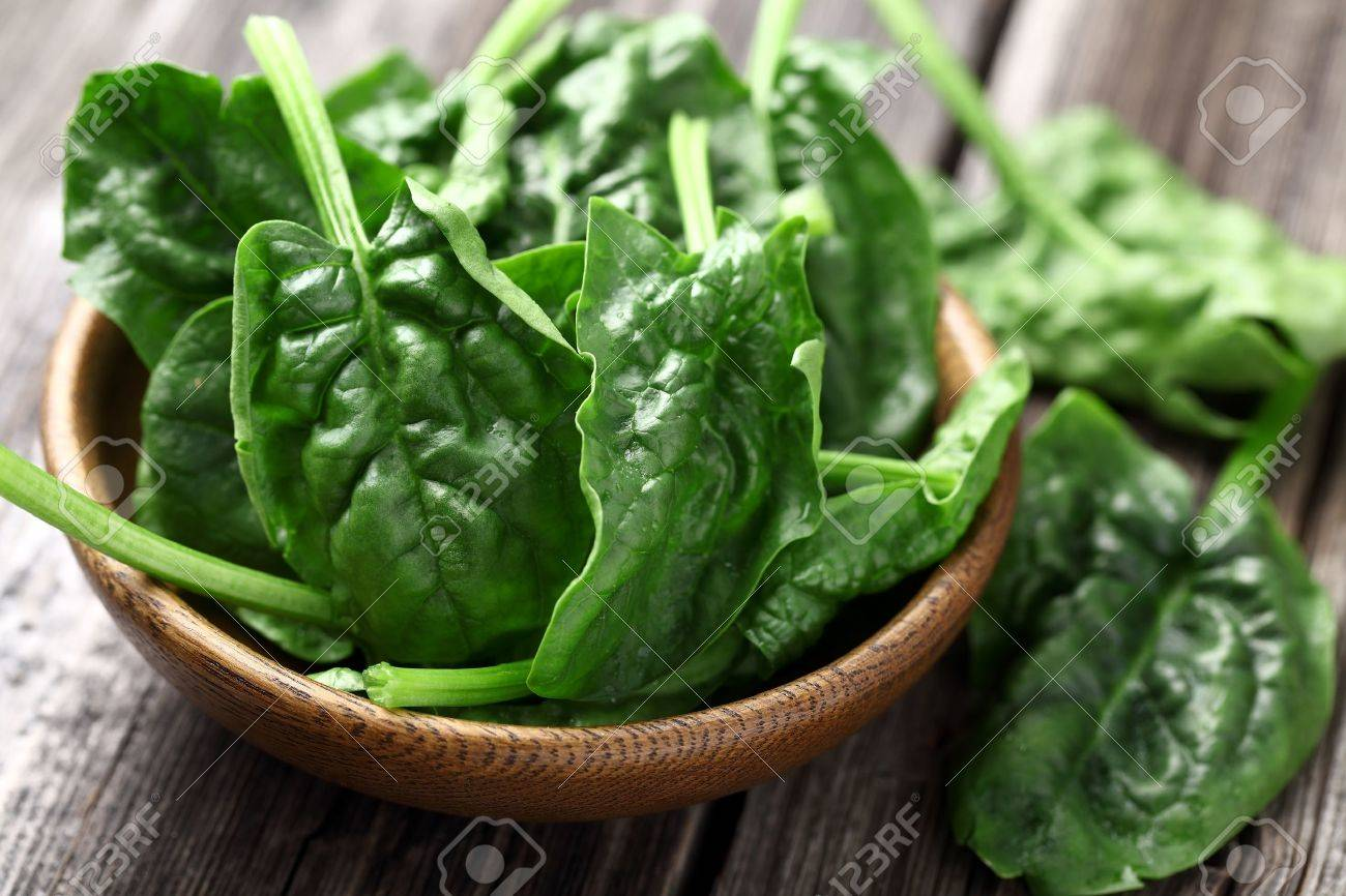 Spinach leaves in a wooden plate - 18818325