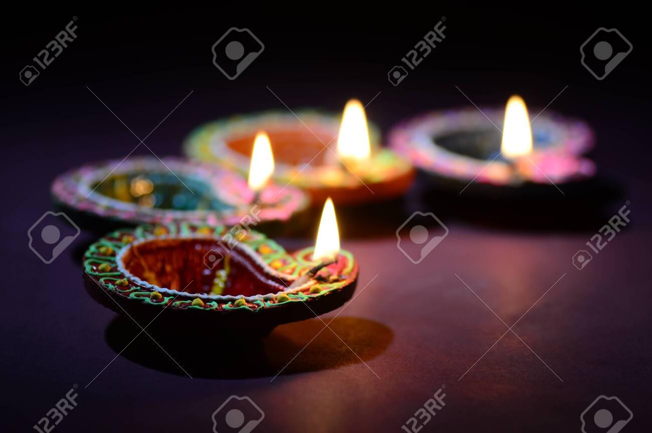 Colorful clay Diya (Lantern) lamps lit during Diwali celebration. Greetings Card Design Indian Hindu Light Festival called Diwali. - 136229168