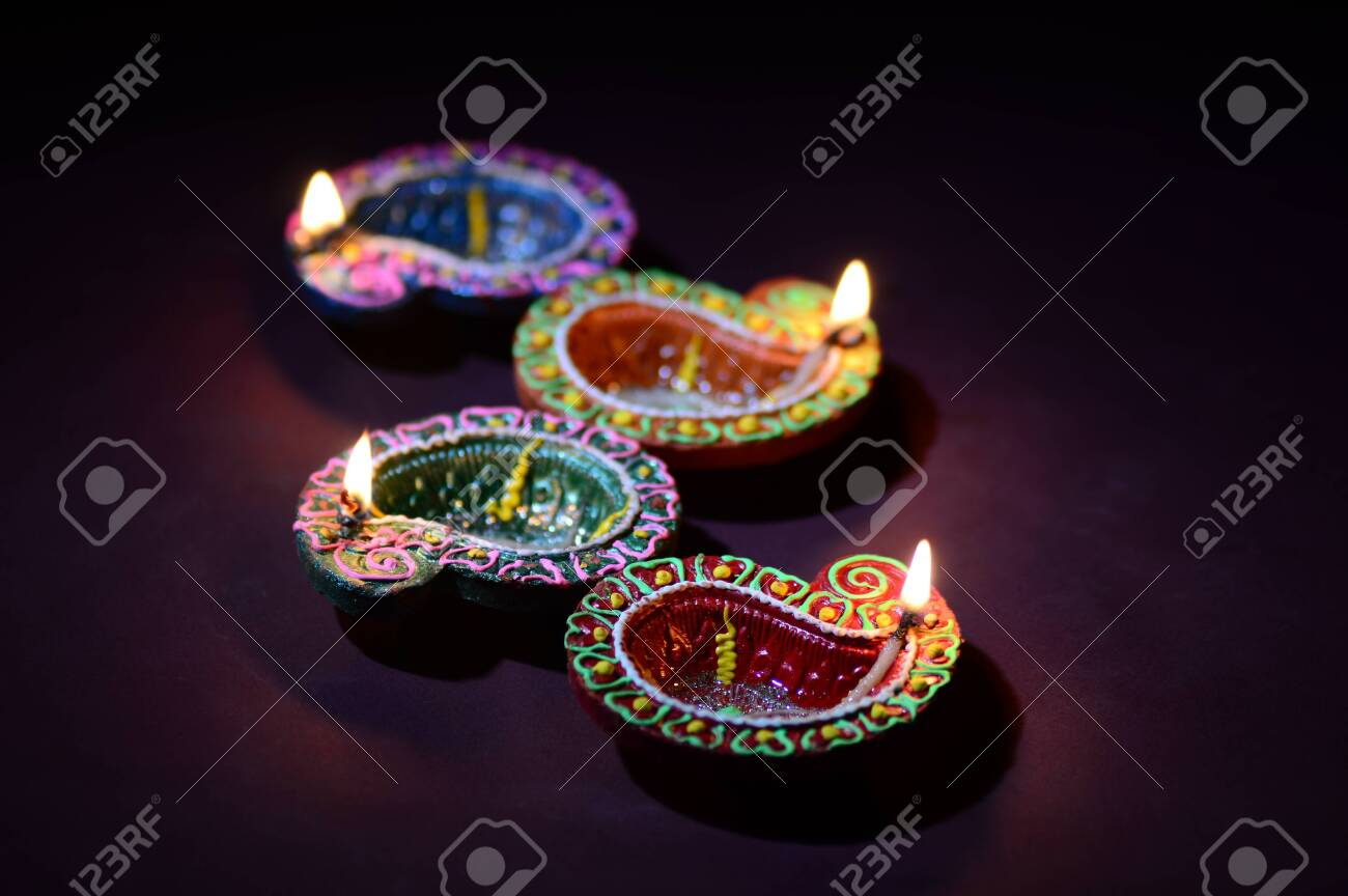 Colorful clay Diya (Lantern) lamps lit during Diwali celebration. Greetings Card Design Indian Hindu Light Festival called Diwali. - 136230378