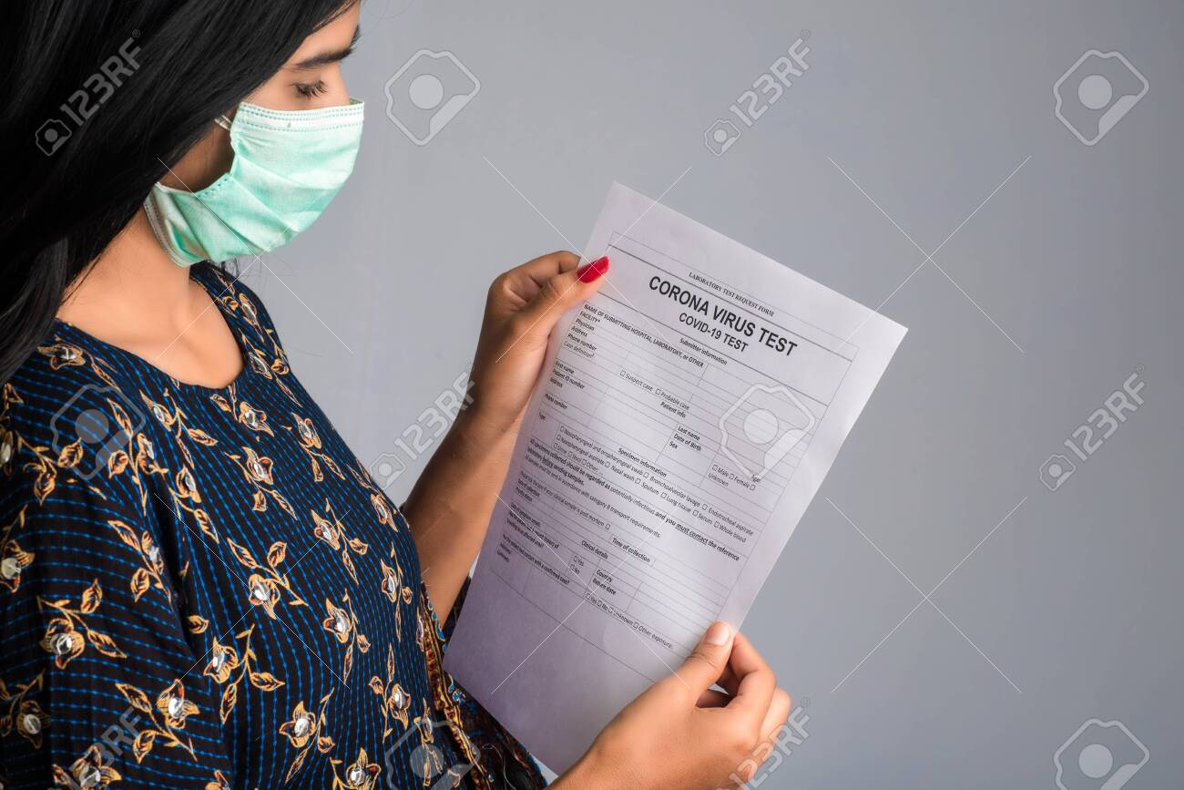 Coronavirus concept for a blood test. A young girl reading or filling a medical test form for coronavirus testing. - 143034700
