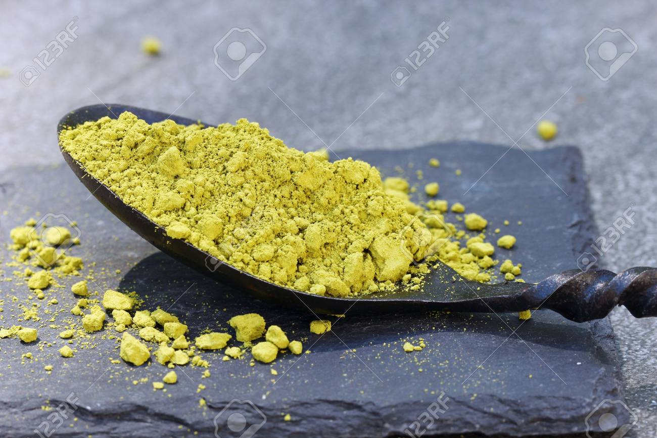 Green Matcha powder in a spoon on a slate colored tile, selective focus Stock Photo - 79744127