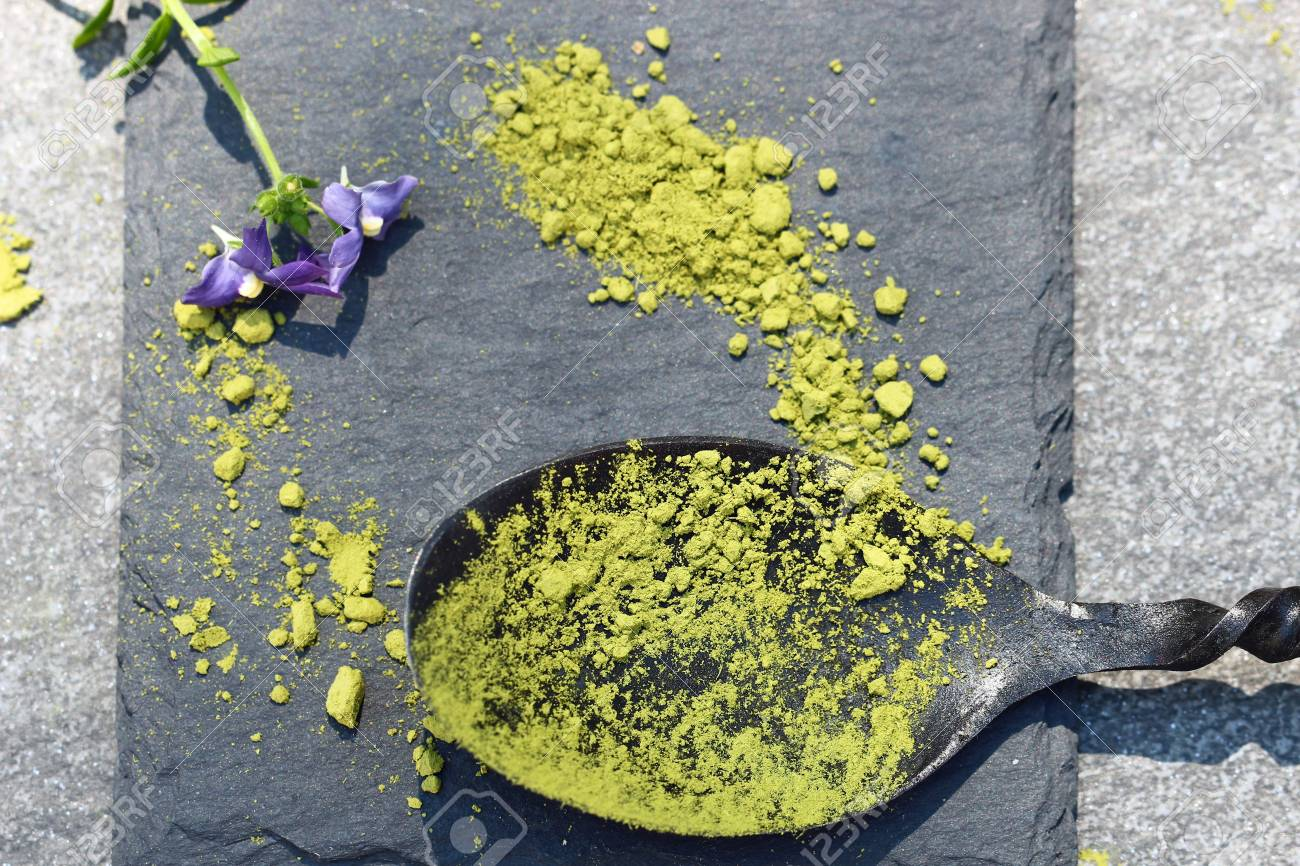 Green Matcha powder in a spoon on a slate colored tile Stock Photo - 79744128