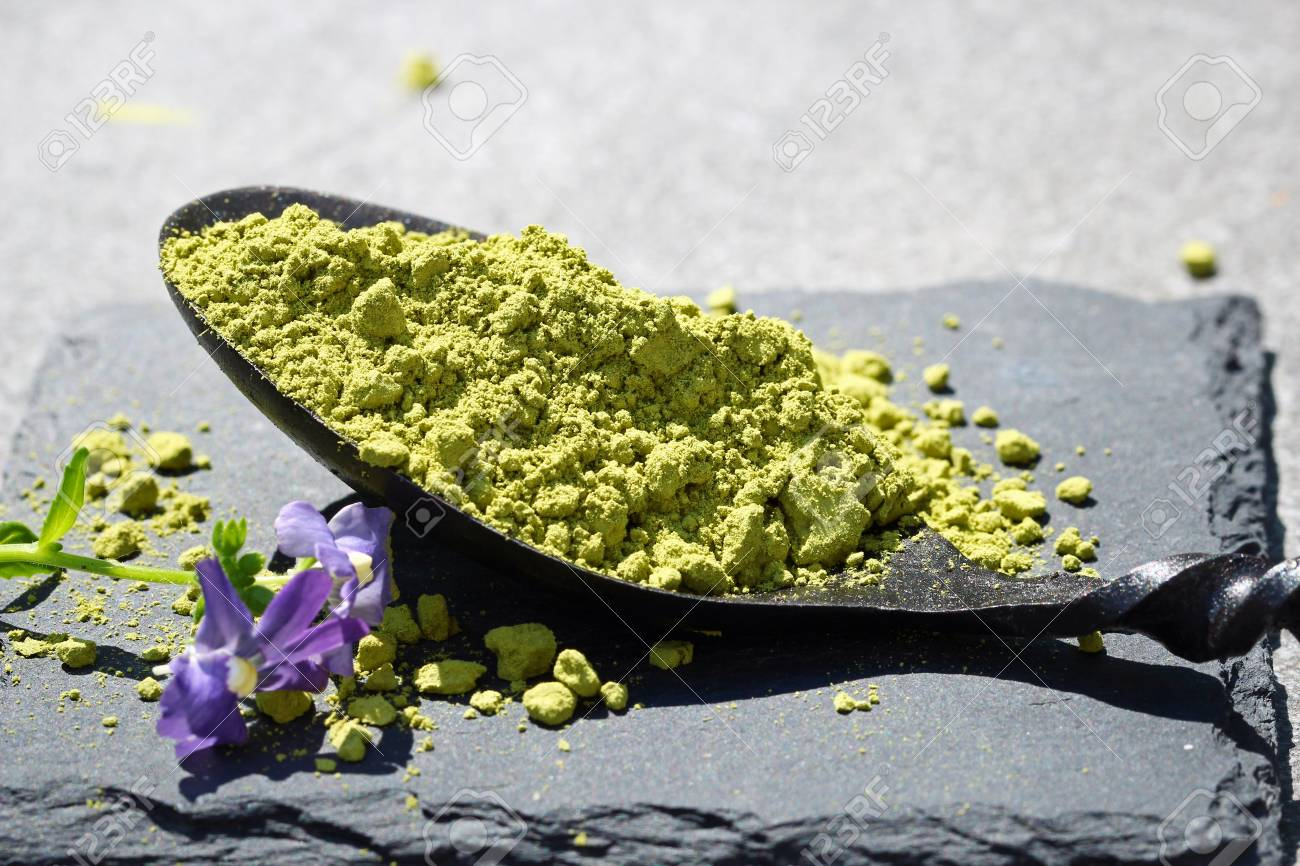 Green Matcha powder in a spoon on a slate colored tile, selective focus Stock Photo - 79744130
