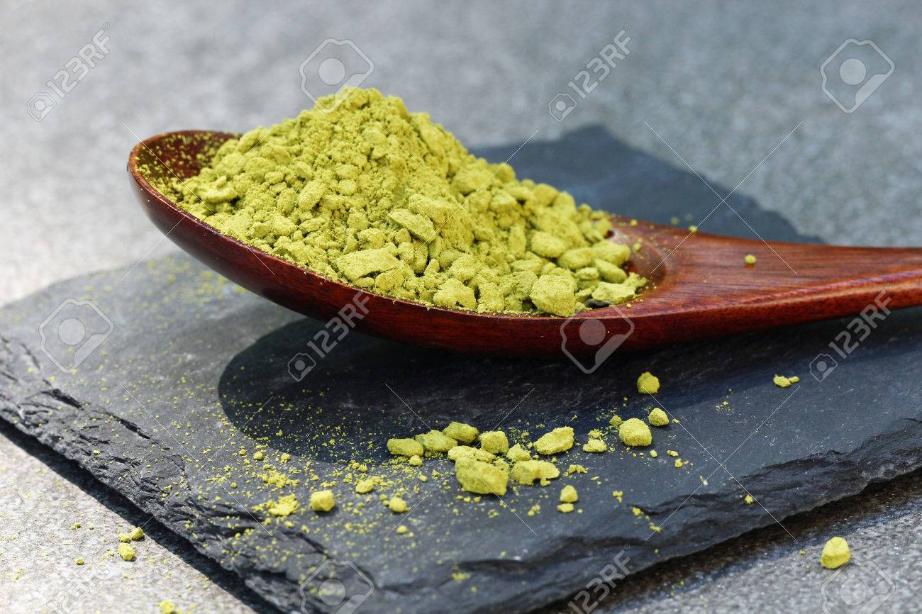 Green Matcha powder in a spoon on a slate colored tile, selective focus Stock Photo - 79744125