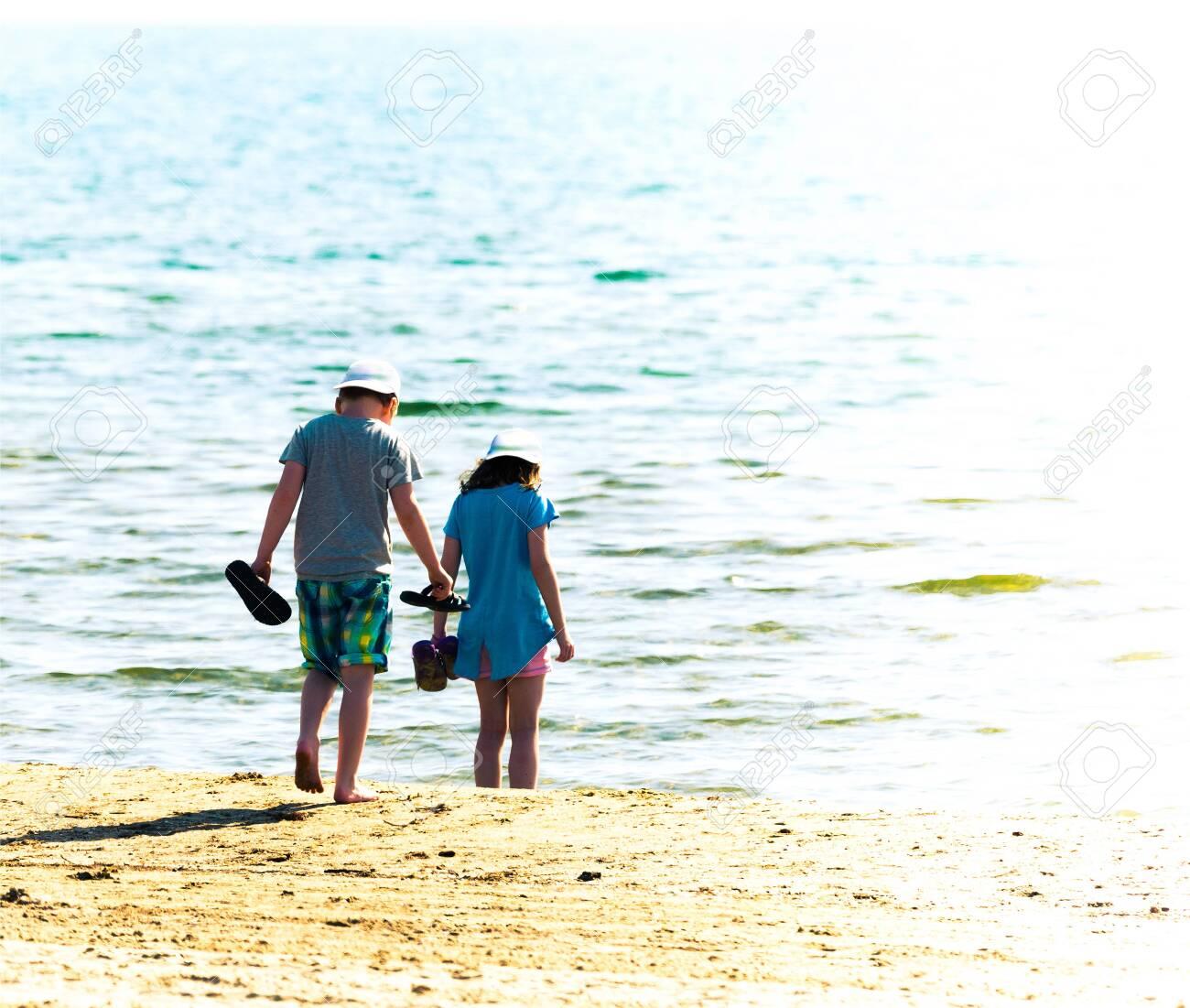 pair of children on sandy beach - 125950132