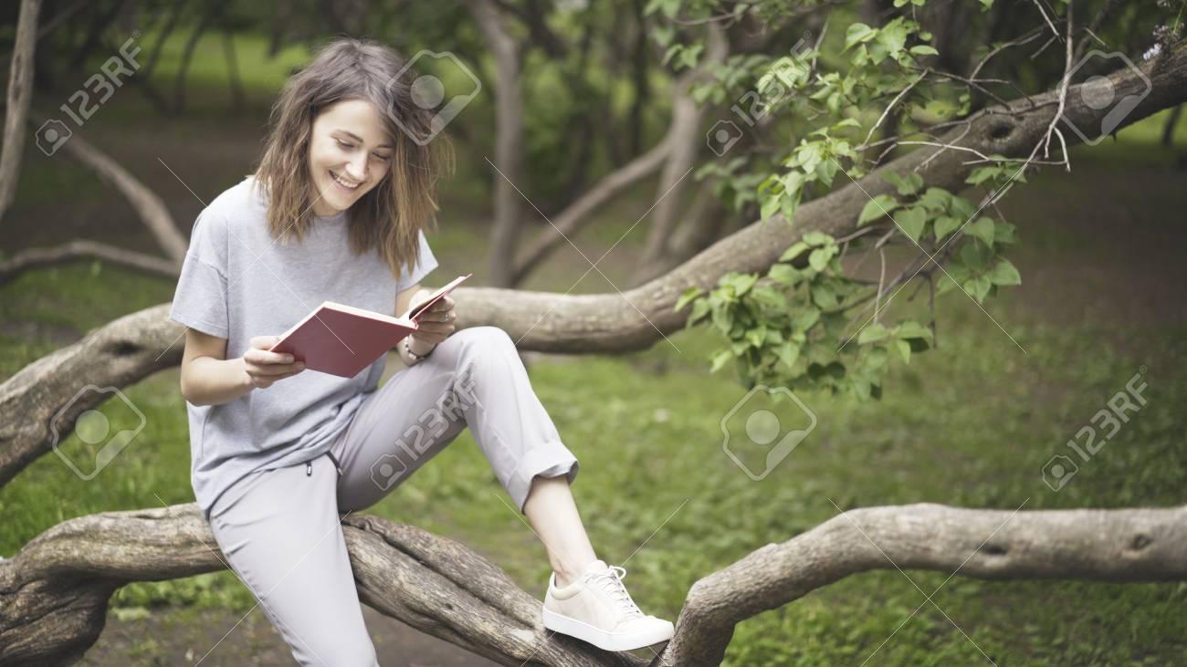 Una Niña Morena Vestida Vestido Blanco Con Una Camisa Gris Está Leyendo Un Libro En El Parque Sentado En Un Tronco De árbol