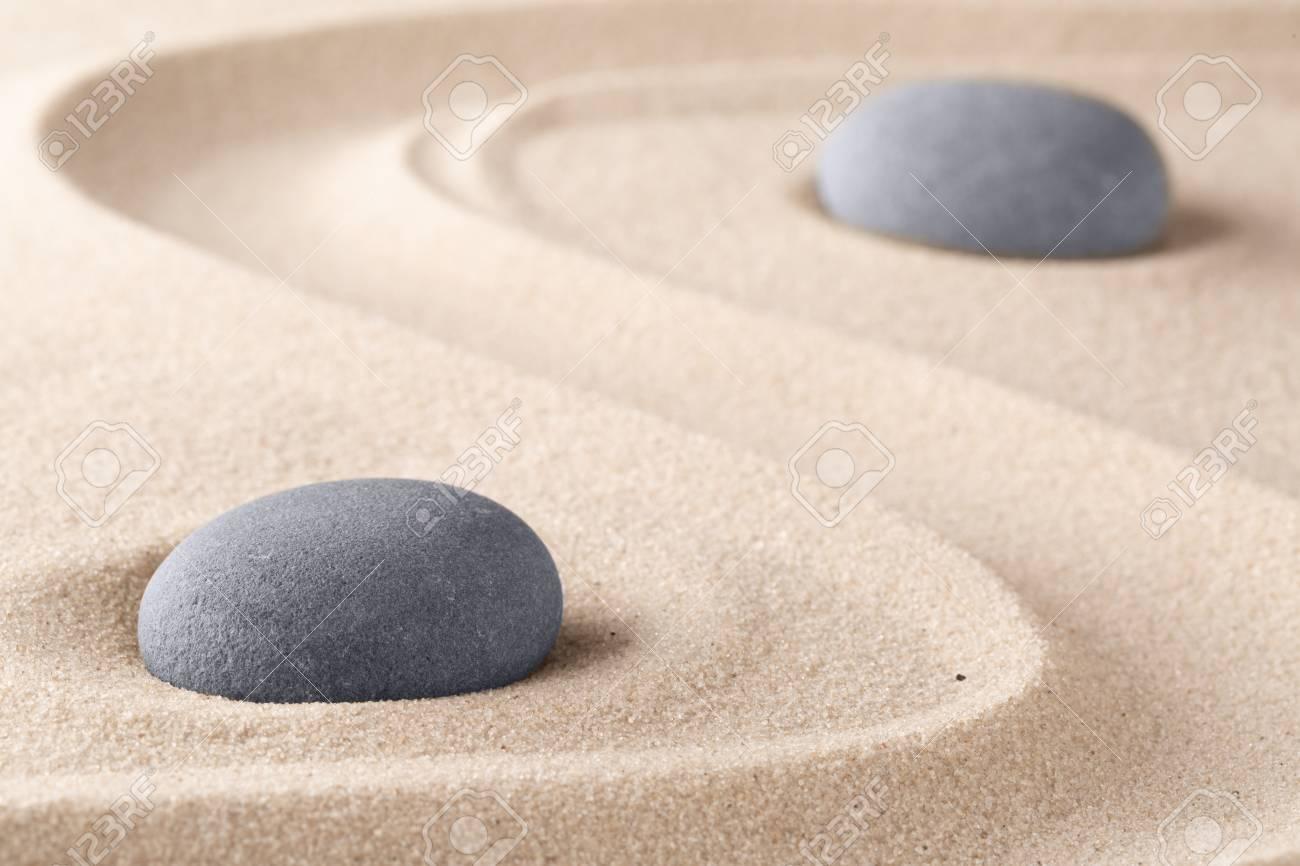 Zen garden meditation stone. Round rock on sandy texture background. Yoga or mindfulness concept. - 125282782