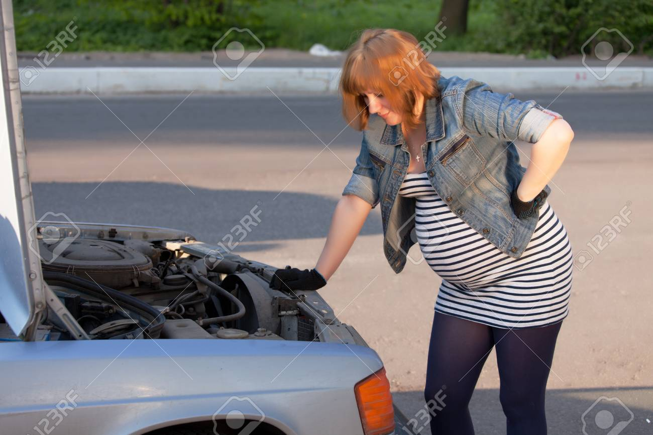 Pregnant Woman Trying to Repair the Car Stock Photo - 13797990