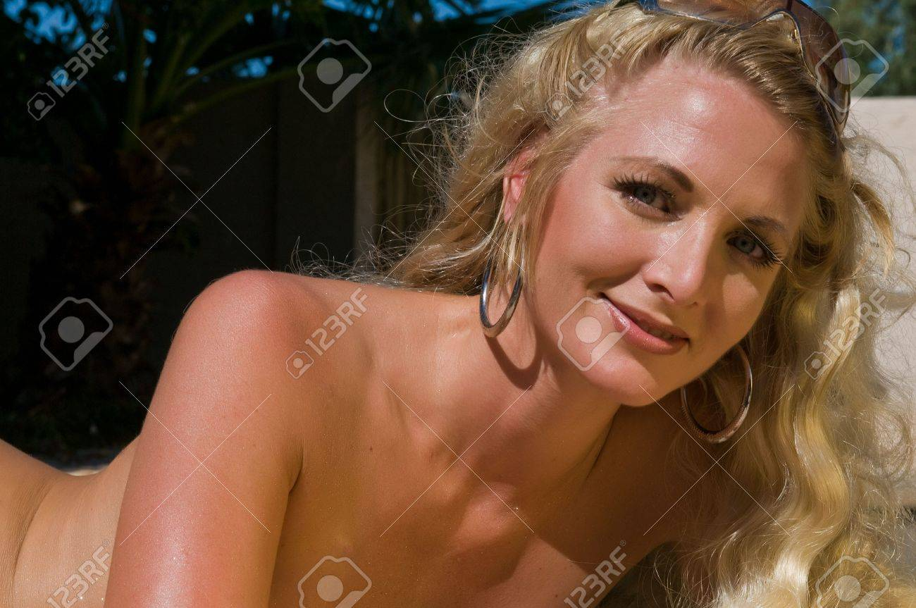 Beautiful mature blonde getting an all over tan by the pool Stock Photo - 5787534