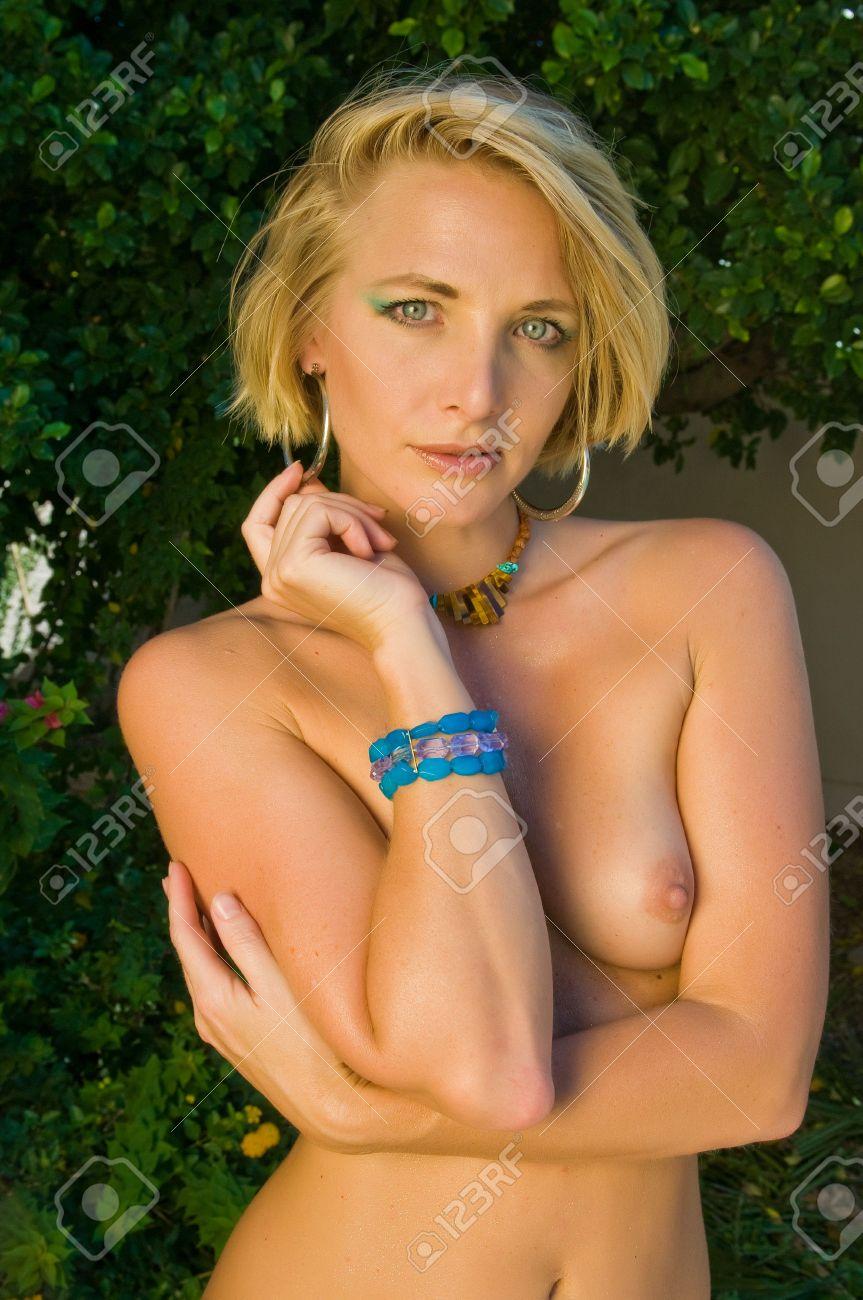 beautiful mature blonde standing nude in her garden stock photo