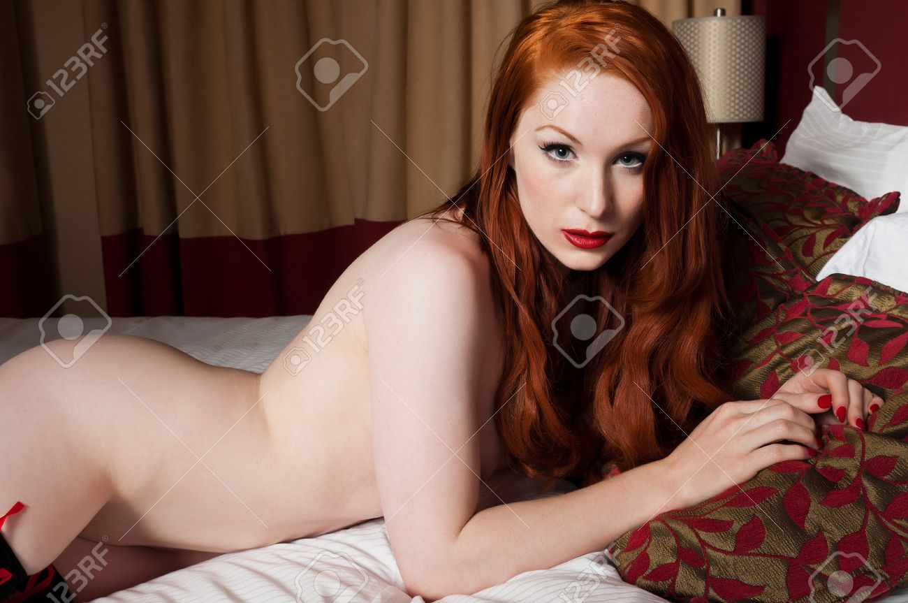 Lovely pale redhead lying nude in bed Stock Photo - 10002519