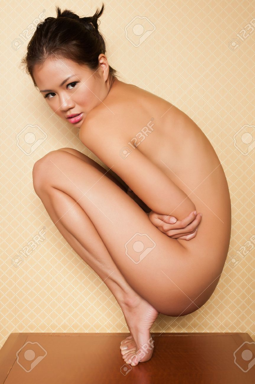 Pretty Singaporean woman sitting nude on a bedroom nightstand Stock Photo - 10084842