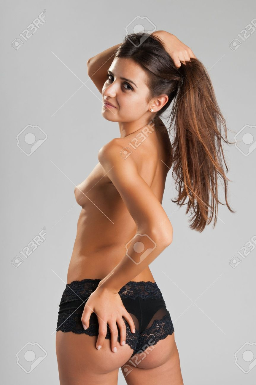 Pretty slender Romanian brunette topless in black panties Stock Photo - 10614386