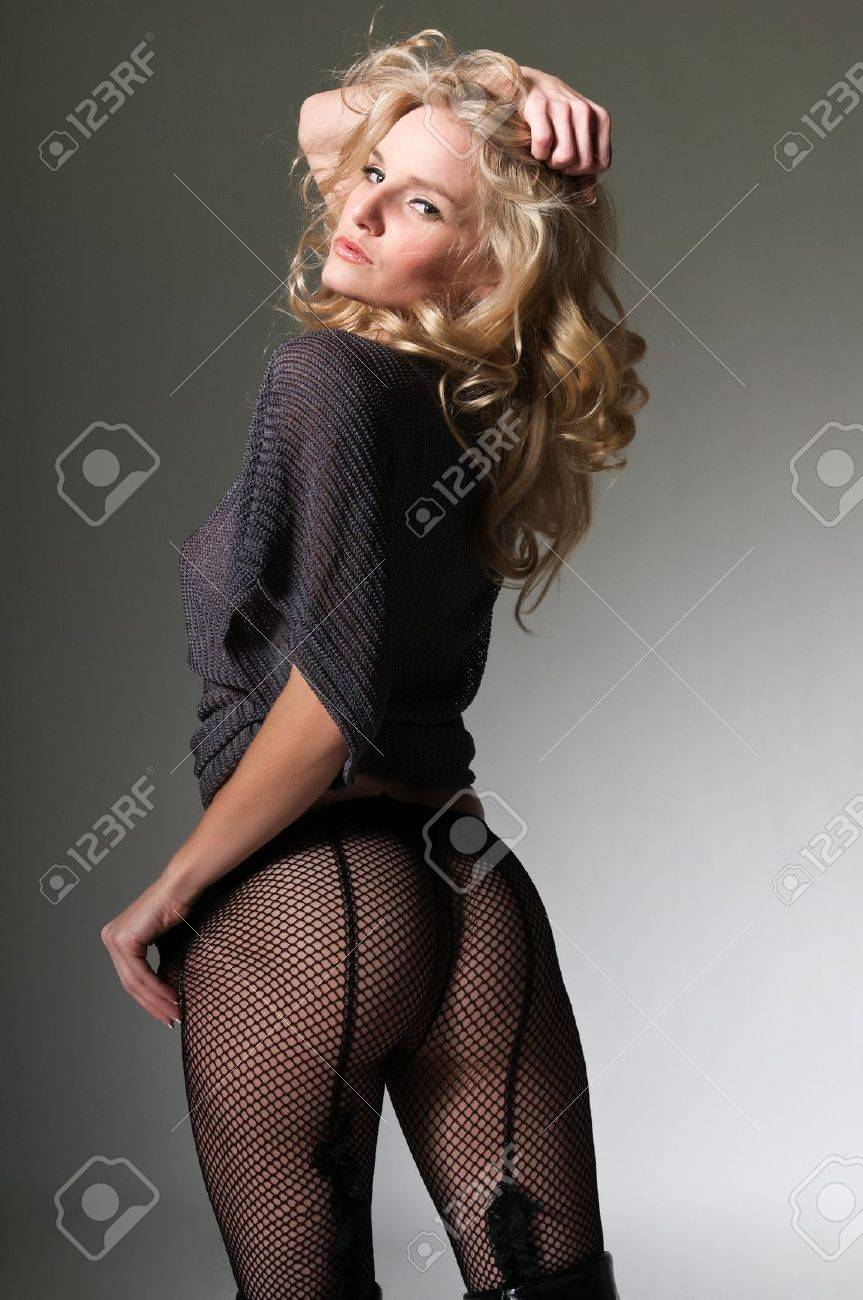 Pretty petite blonde in a gray sweater and fishnets Stock Photo - 11599795