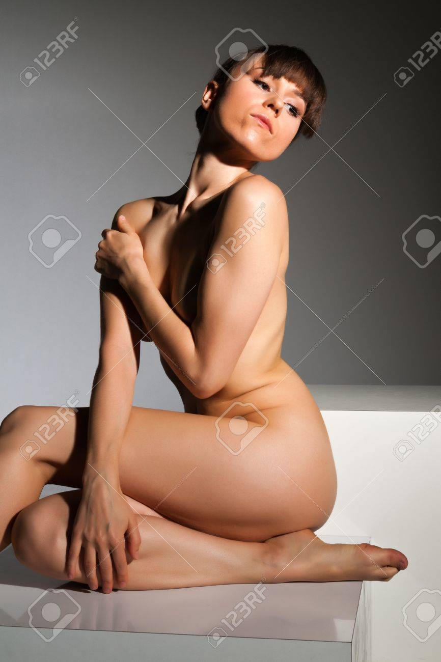 Petite nude brunette sitting on a white block Stock Photo - 14120455