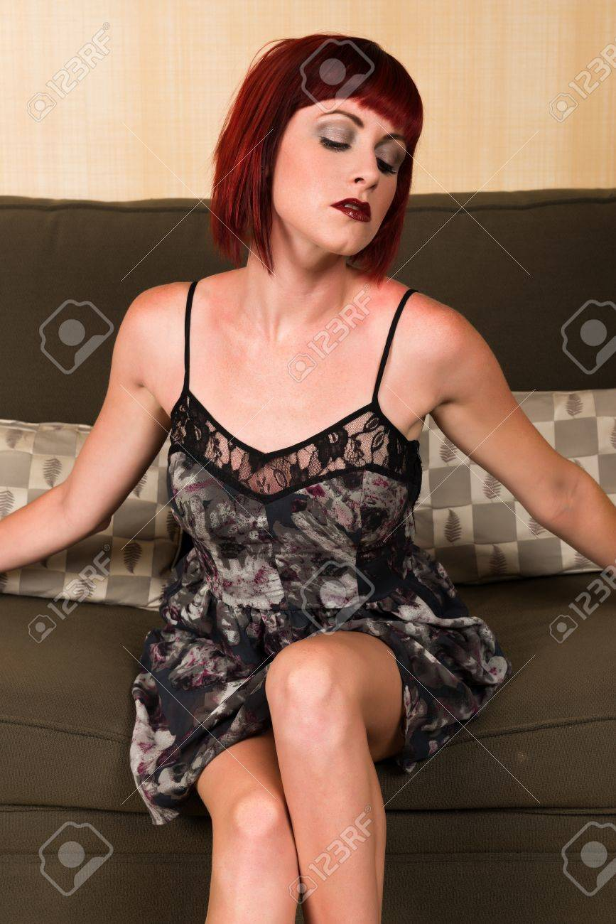 Pretty petite redhead sitting on a green couch Stock Photo - 21086125