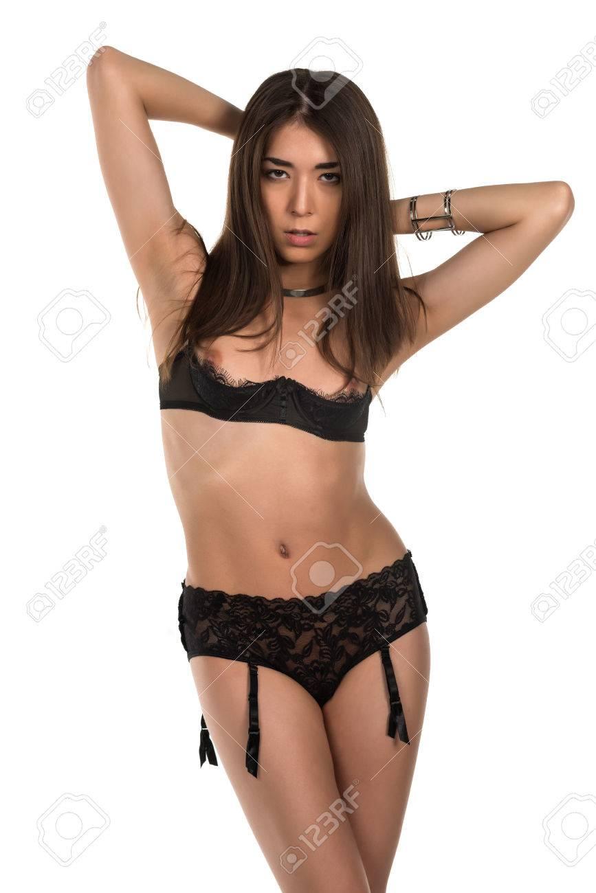 b7e20b47710 Beautiful petite Eurasian woman in revealing black lingerie Stock Photo -  38544053
