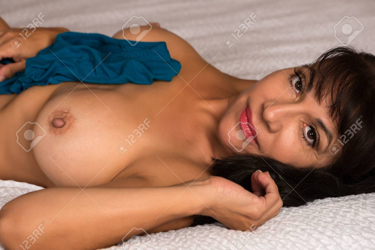 pretty mature brunette lying nude in bed stock photo, picture and