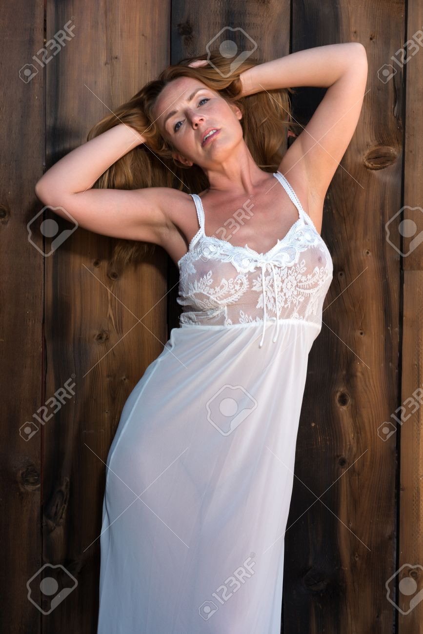 beautiful tall redhead in a white lace negligee stock photo, picture