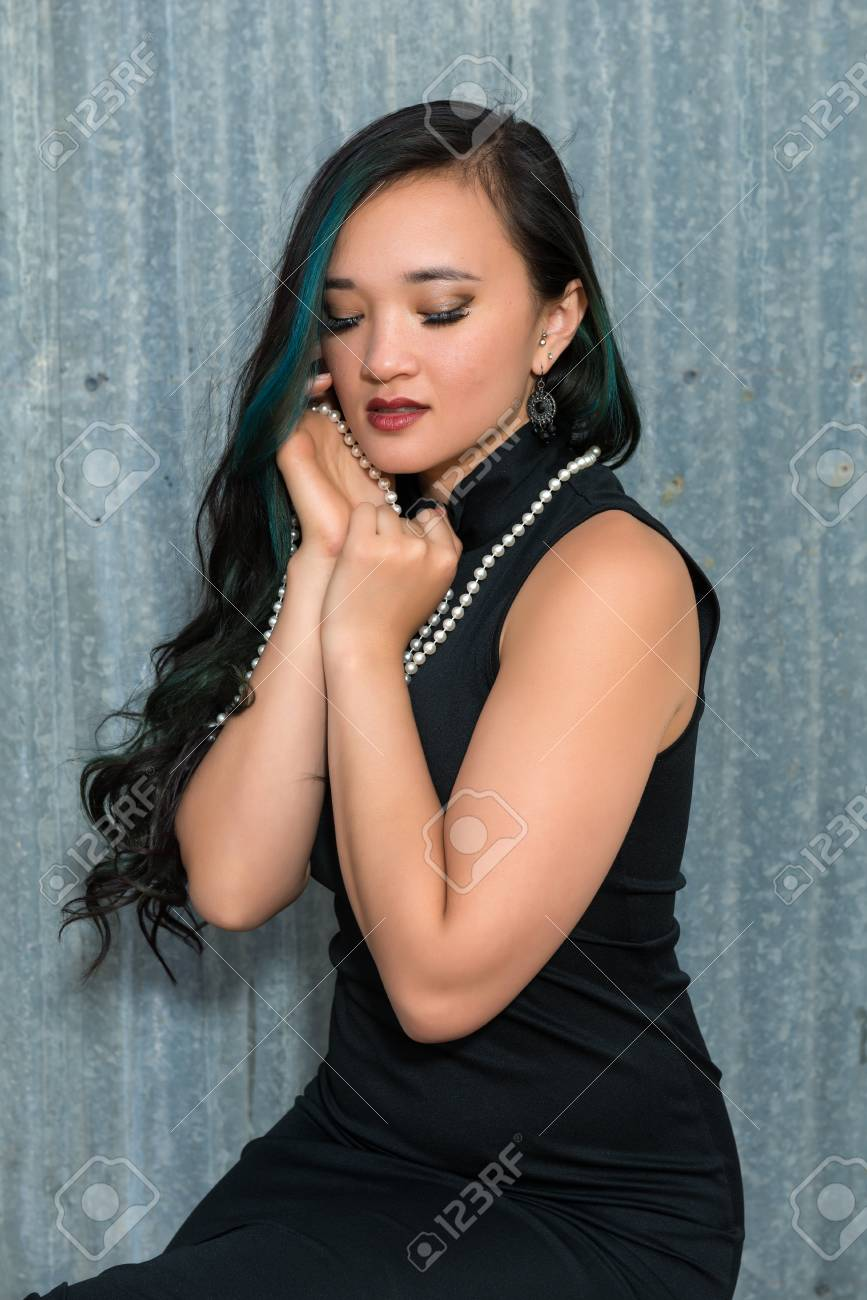 bca9dee661d Pretty young brunette in a black dress and pearls Stock Photo - 80608566