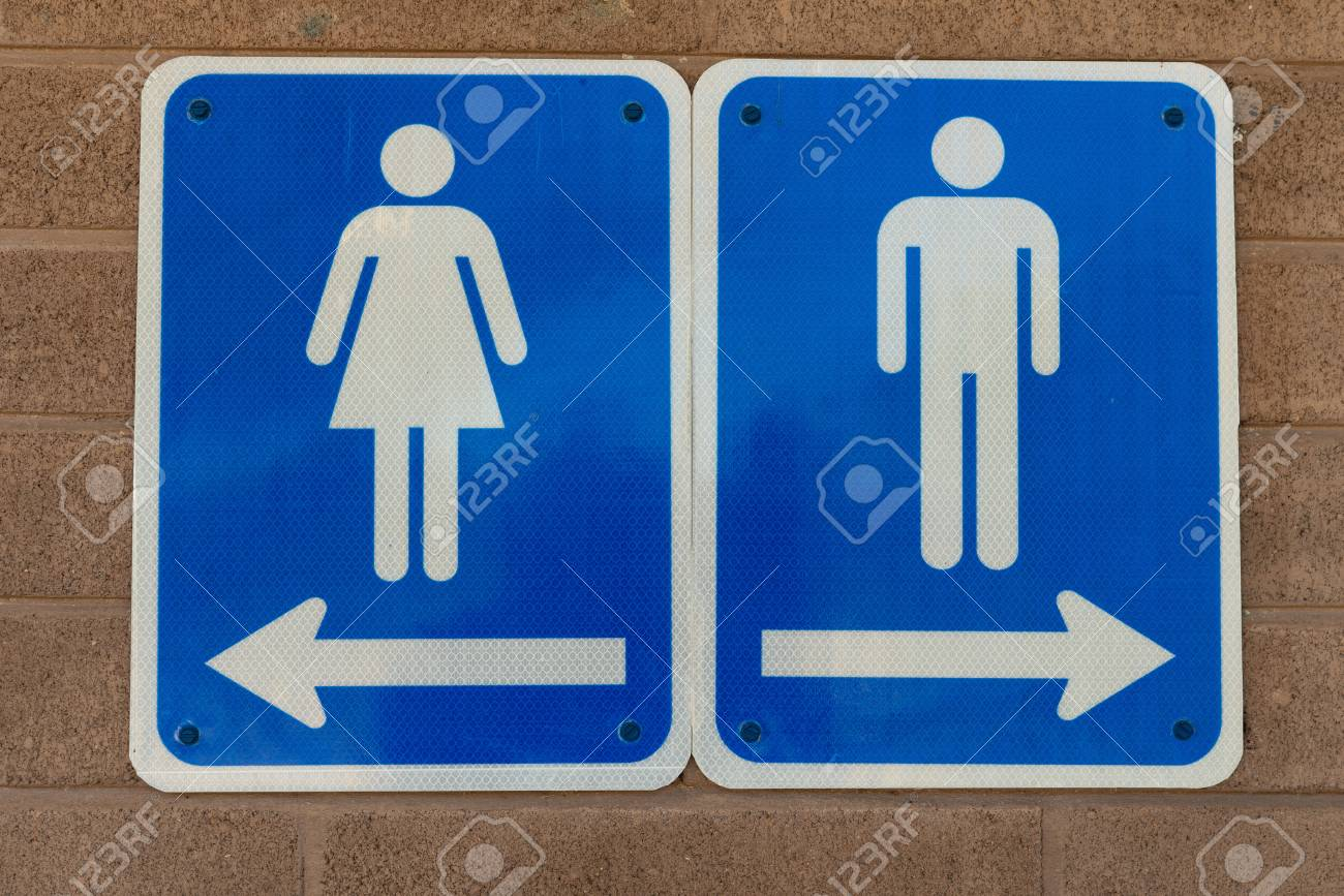 Mens and womens restroom signs bolted to a brick wall stock photo 100053211