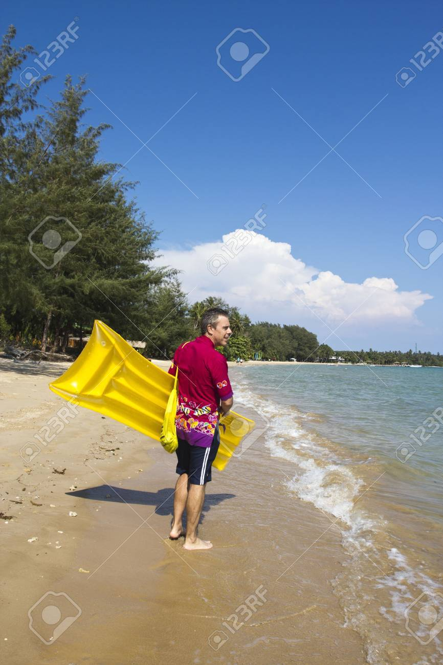 The  European man walking and carrying a yellow rubber mattress at the beach at Koh Mak island, Trat, Thailand Stock Photo - 12803212