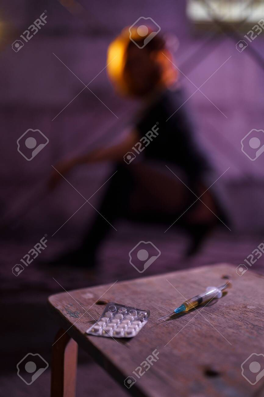 Filled Syringe and Pills on a table - Underground nightclub party dancing of drug addiction redhead caucasian white young woman wearing black sweater, skirt and chocker - Pills and tablets - 122005316