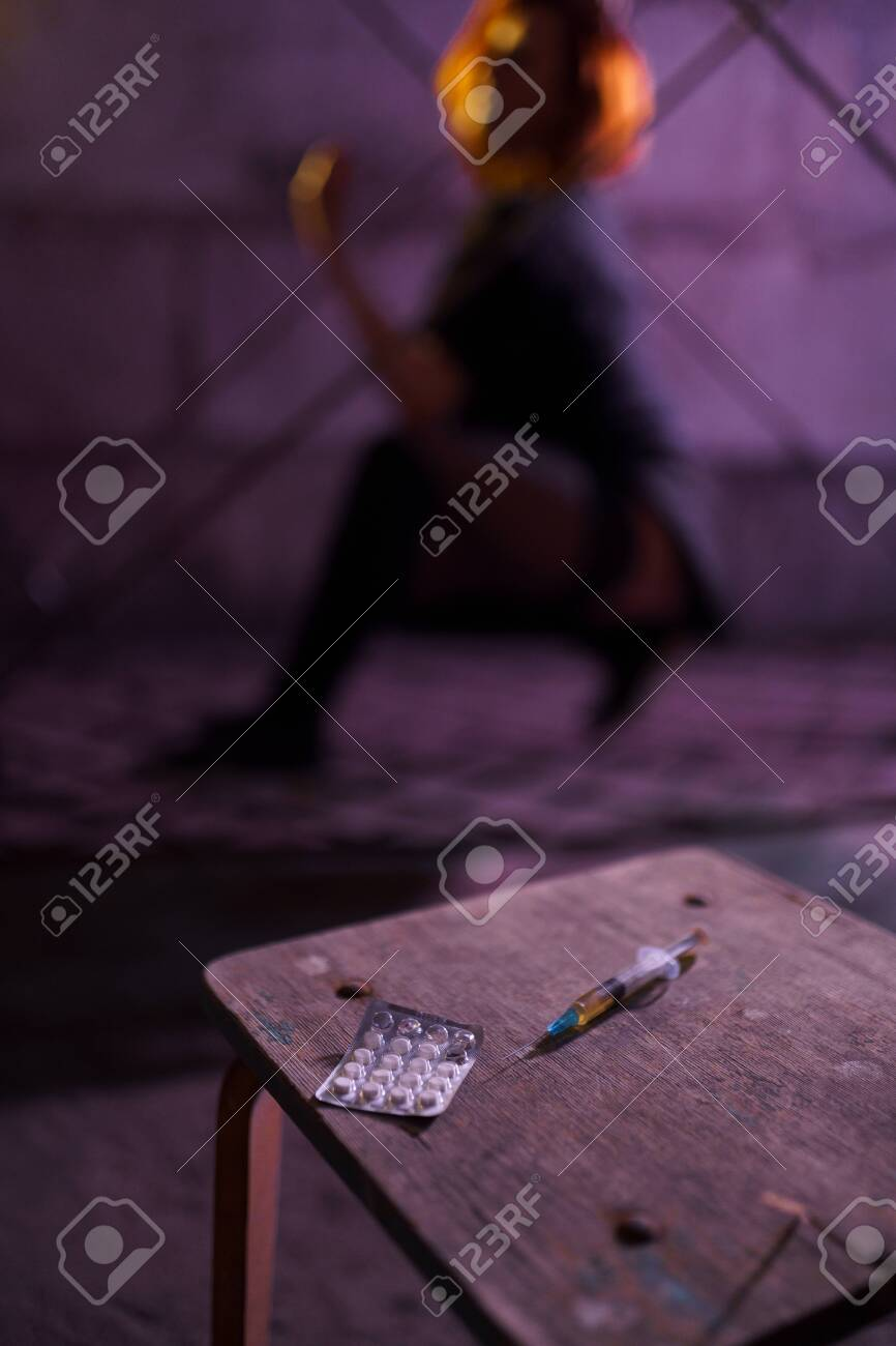 Filled Syringe and Pills on a table - Underground nightclub party dancing of drug addiction redhead caucasian white young woman wearing black sweater, skirt and chocker - Pills and tablets - 122005325
