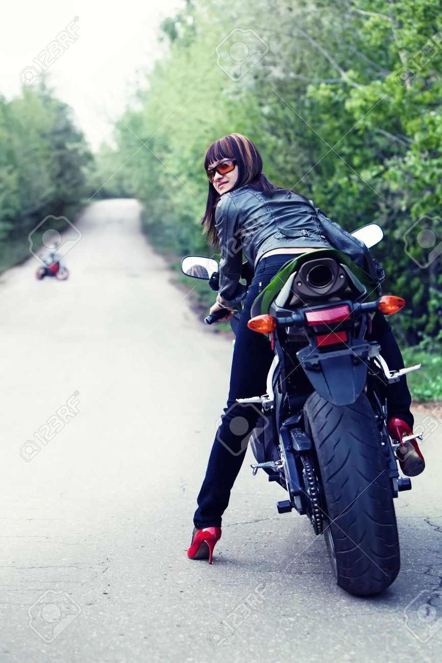 Pretty girl in the leather jacket is looking back sitting on the modern sport motorbike. Another biker on the background