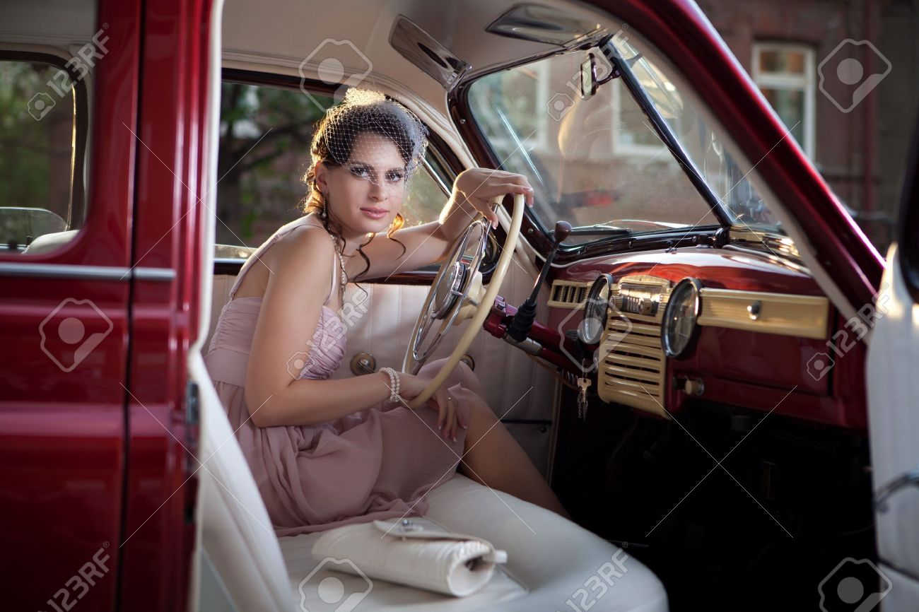 Pretty woman is sitting in the vintage car. Stock Photo - 13487110
