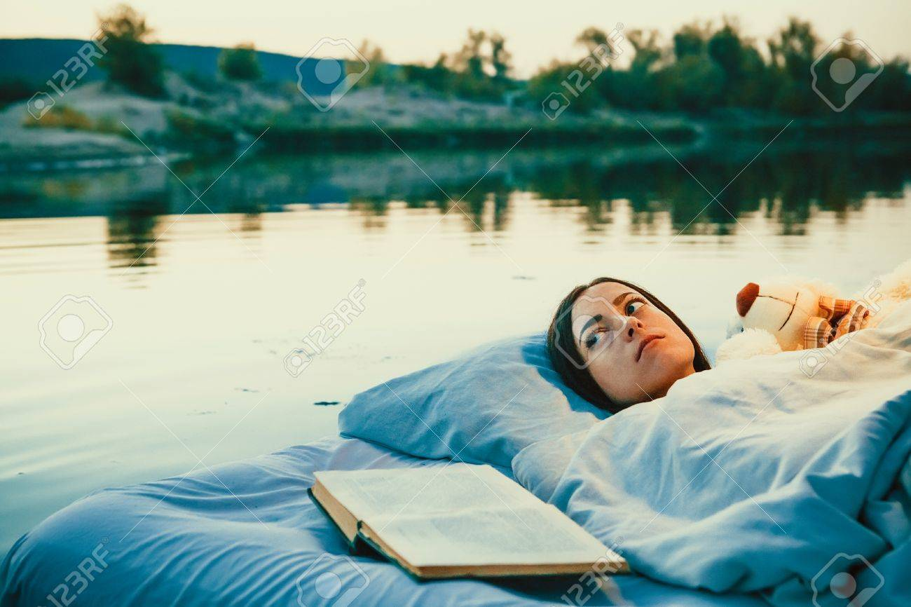 photo pretty woman is laying on the floating bed with a book and toy