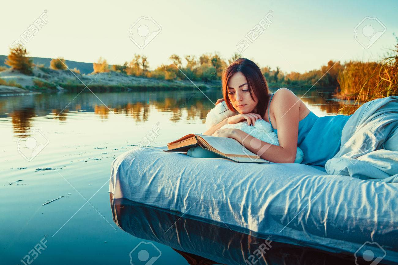 photo pretty woman is laying on the floating bed and reading a book summer sunset on the background