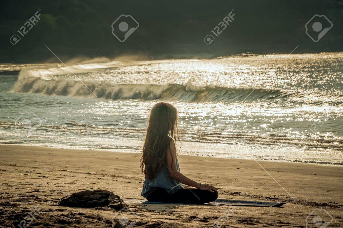 young woman yoga meditation on sunset beach. Gokarna, India - 74472079