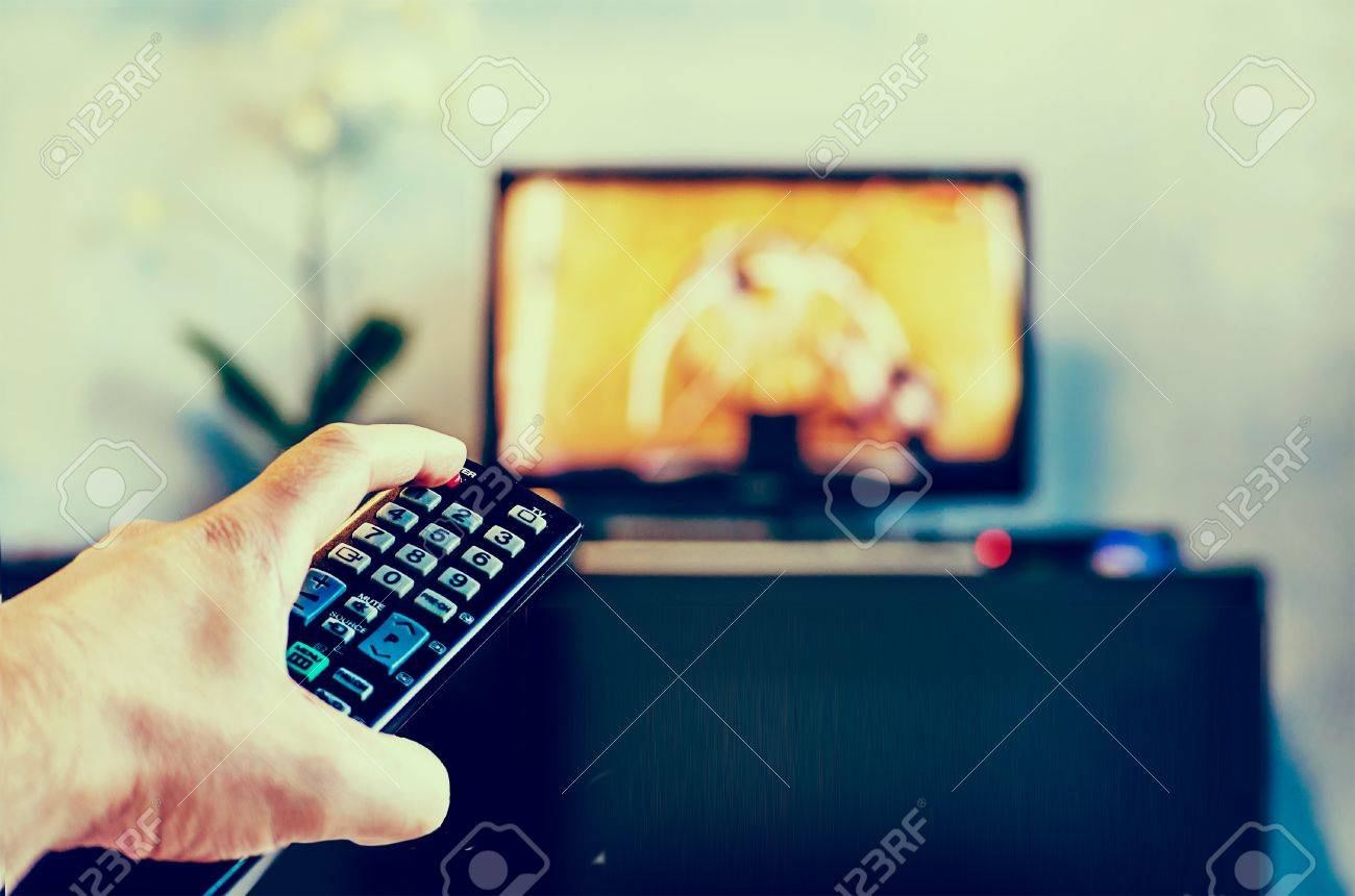 Men with the remote control front of the television. Photo toning in a retro style. - 77471640