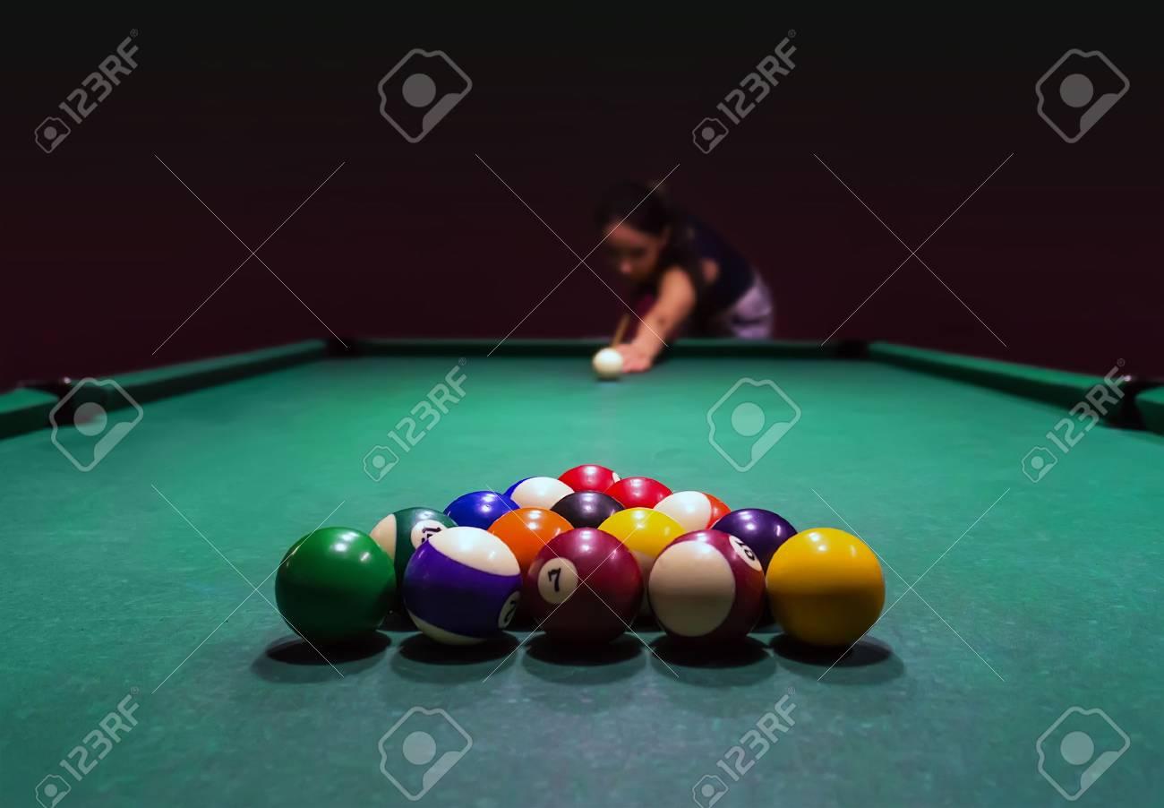 Beautiful girl plays pool in pub and enjoys nightlife - 79668100