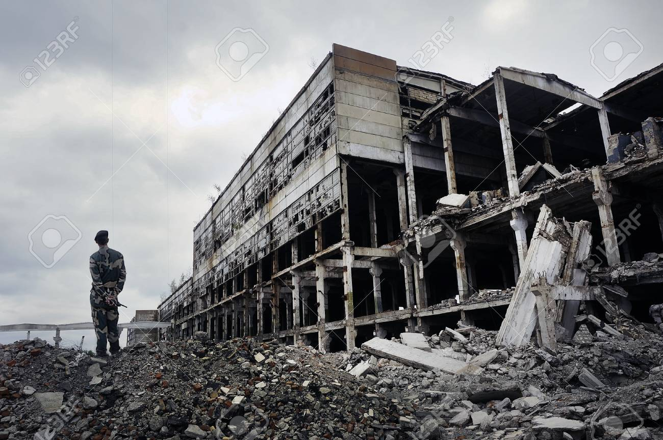 Soldier in military uniform stands on the ruins of the destroyed house. Hot spots on the planet. The concept of the fight against terrorism. - 79429439