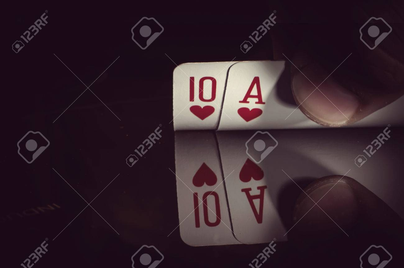 hand holding best classic winning blackjack combination ten and ace hearts - 83878792