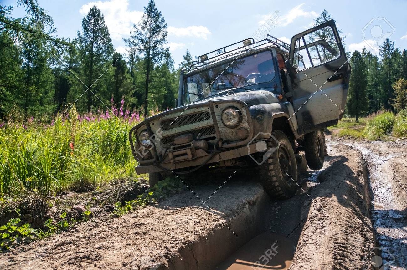 SUV stuck in a rut on a bad impassable road in the woods of Siberia. Russia - 84211609