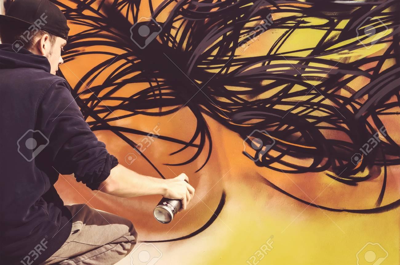 Jeune Peintre Urbain Pulvériser De La Peinture Aérosol Pour Les Graffitis Chez Les Jeunes Garçons Un Artiste De Rue Peint Des Graffitis Sur Le Mur