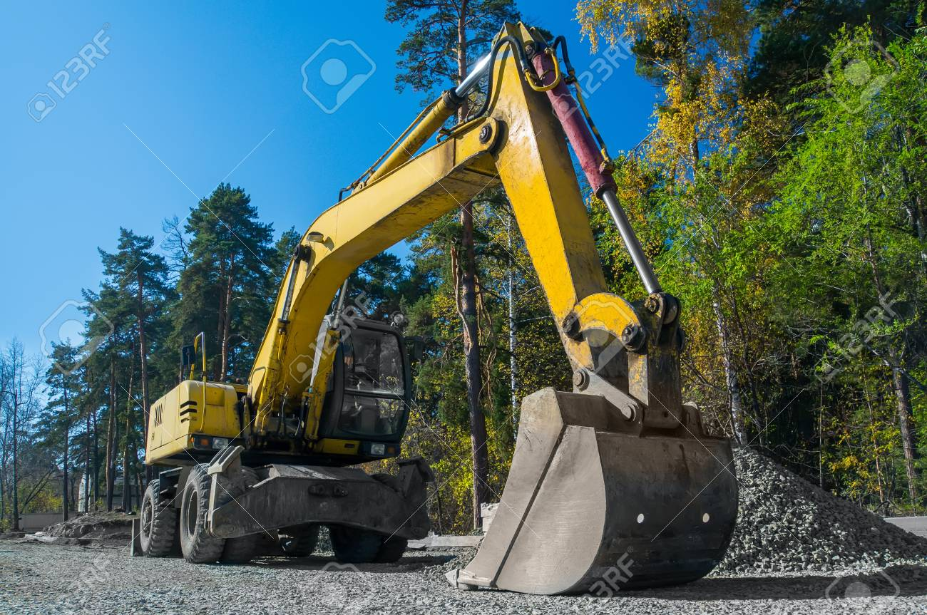 Road repair, asphalt laying. Yellow wheeled excavator - 88117626