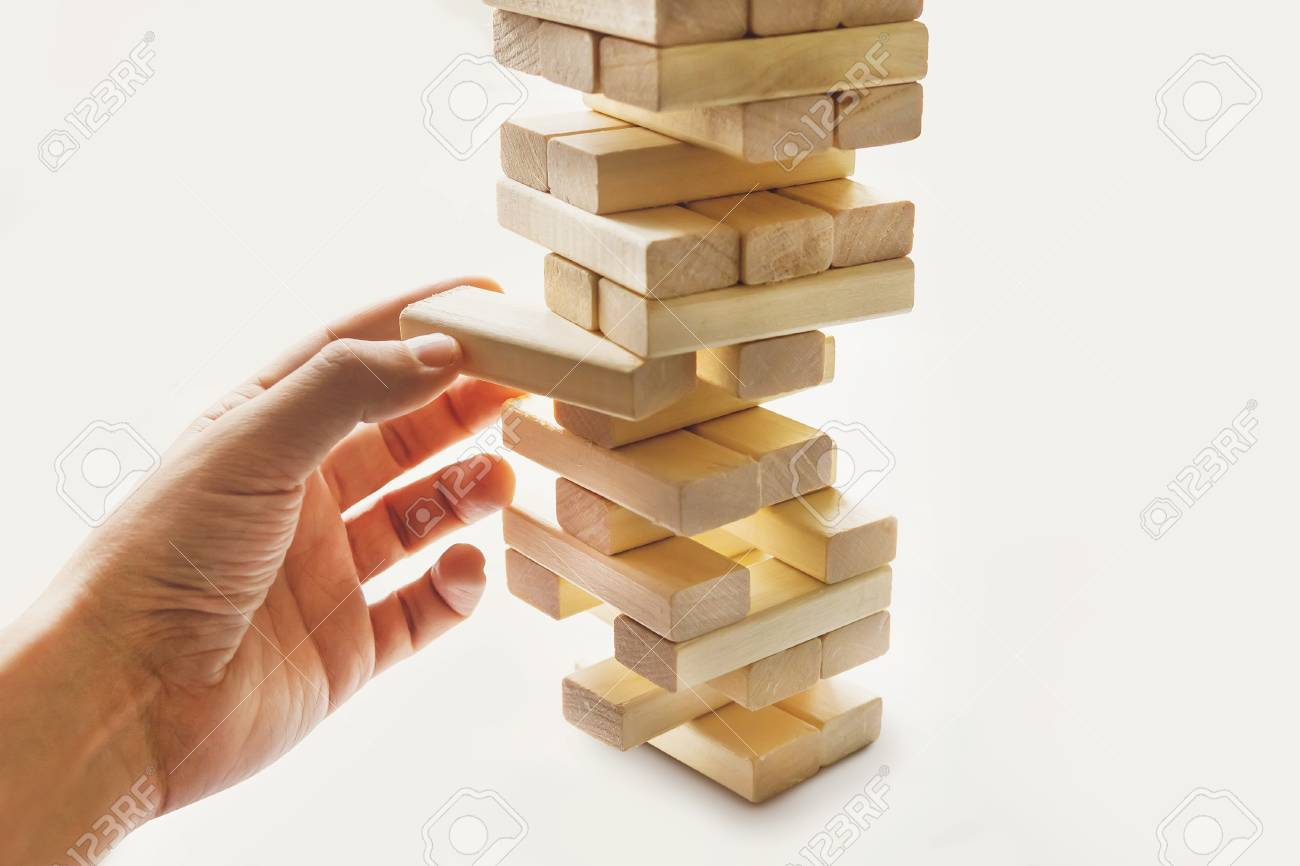 The tower from wooden blocks and man's hand take one block. The game of dice on white background.. - 89853738