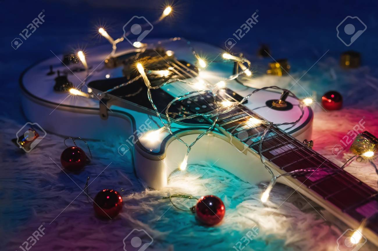 Electric guitar with lighted garland on dark background. Gift guitar classic shapes for Christmas or new year. - 90018660
