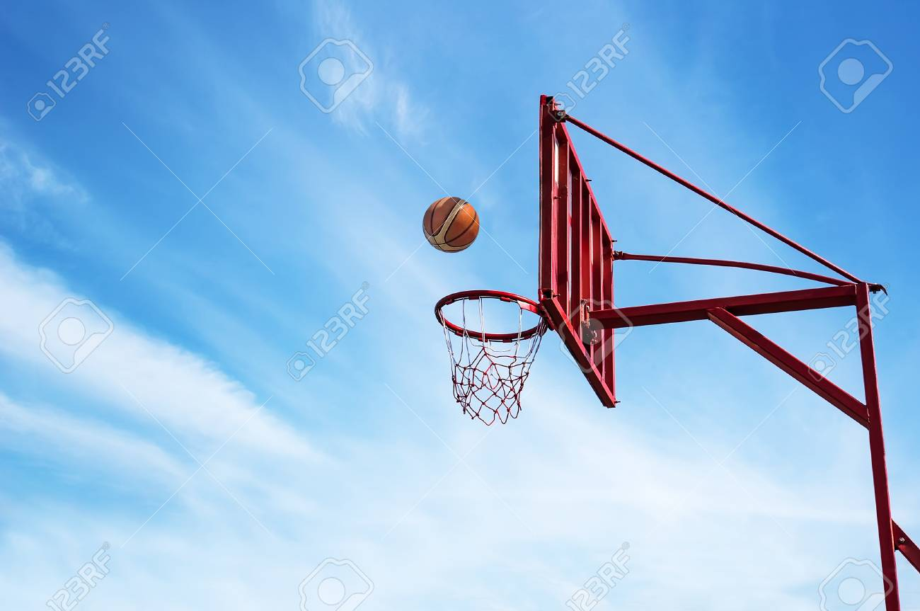 Old Basketball ring on blue sky background with ball into a basket. - 92503357