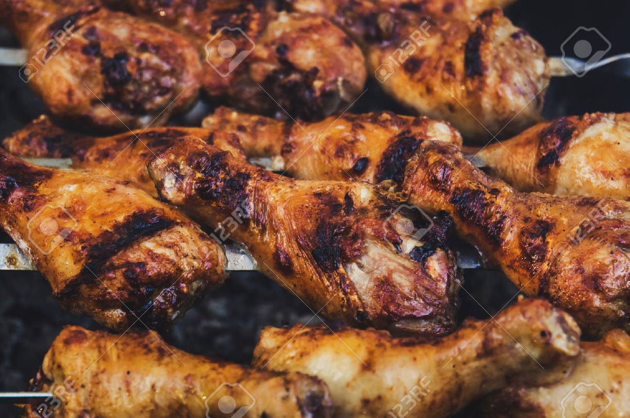 grilled chicken on a skewer with a delicious crispy fried crust. The view from the top. Hot BBQ Charcoal Flaming Grill Close-up. - 92507861