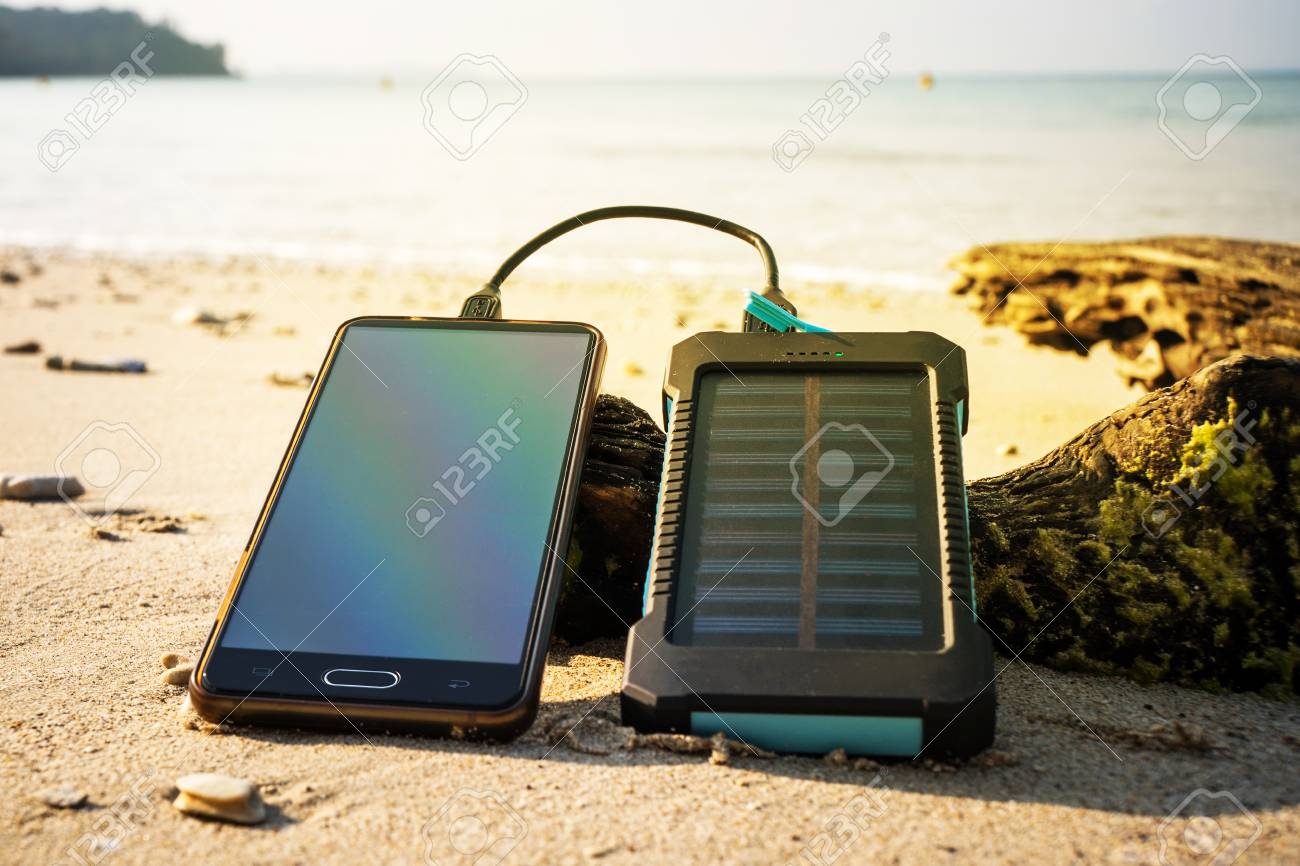 Battery solar energy device on a background of the sandy beach of an uninhabited island. Charge smart phone from the solar battery. - 103330186
