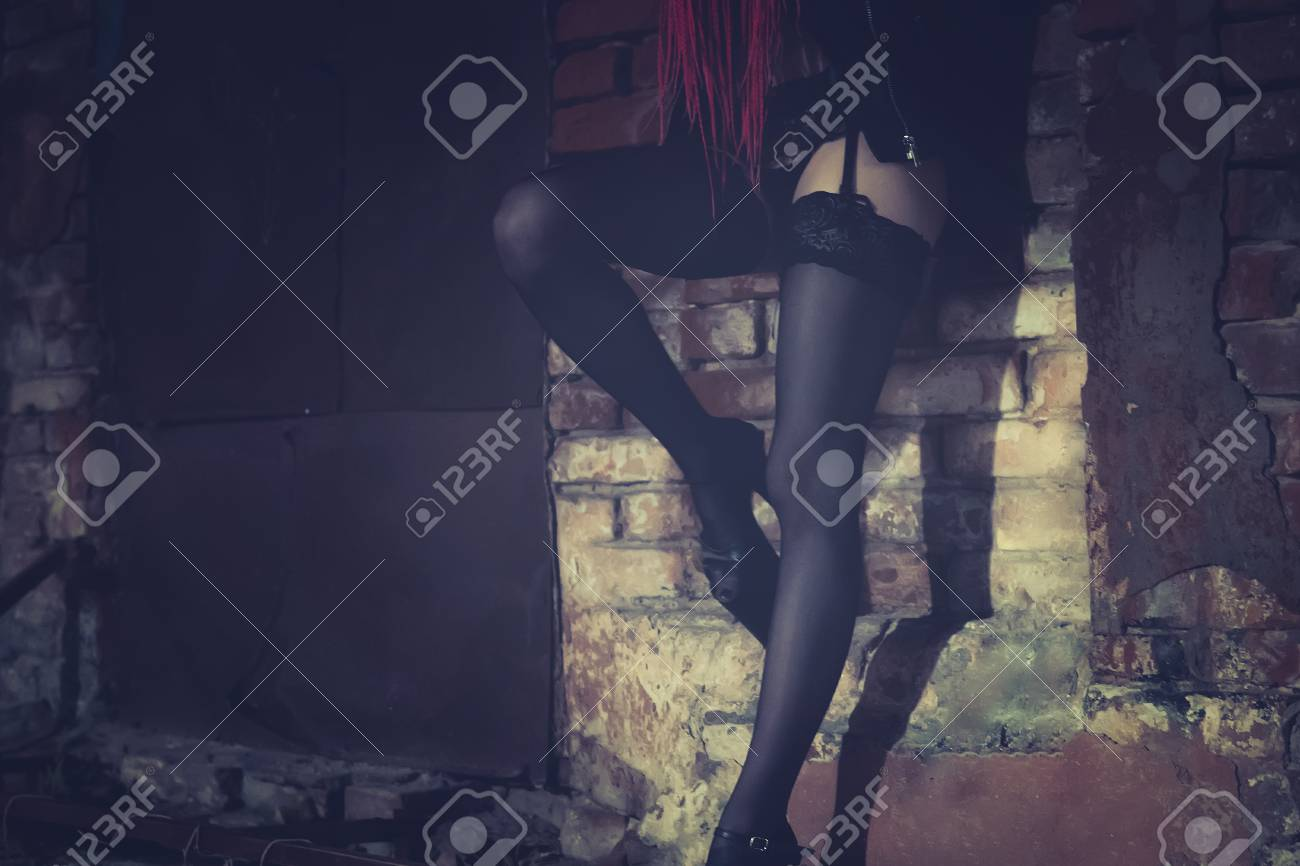 Female working on the night street. girl stands at the old brick wall bending her leg in a seductive pose. - 106918799
