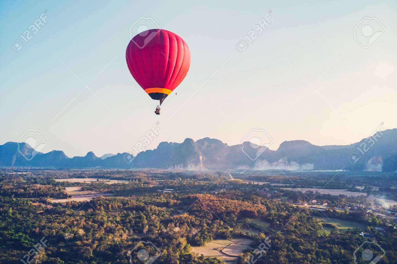 red hot-air balloon raising just in time to explore the beautiful sunset over Vang Vieng in Laos, Southeast Asia. - 123546603