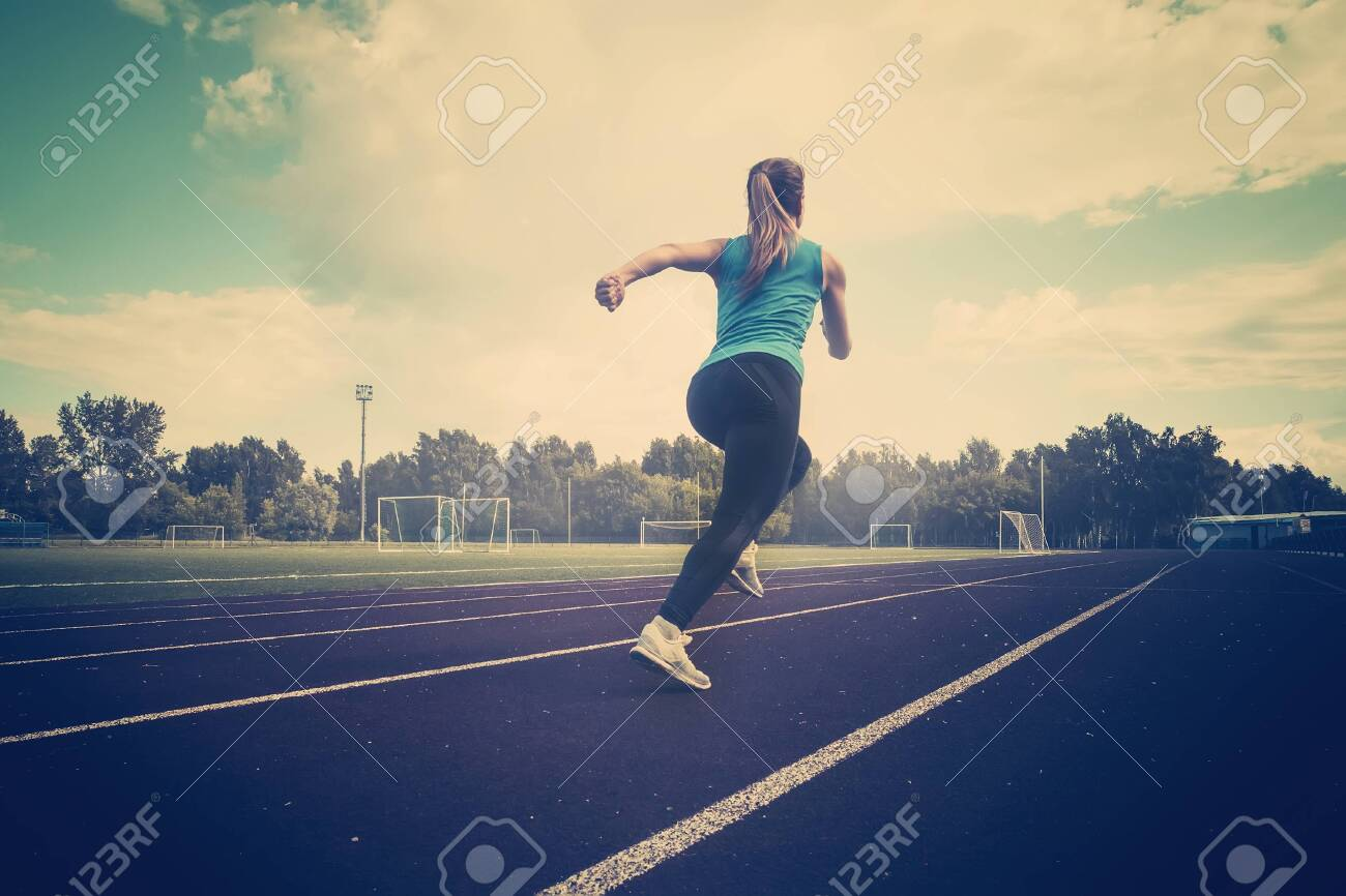 young fitness woman runner running on track. A young athlete runs in sportswear at the stadium in the early morning. - 126576280