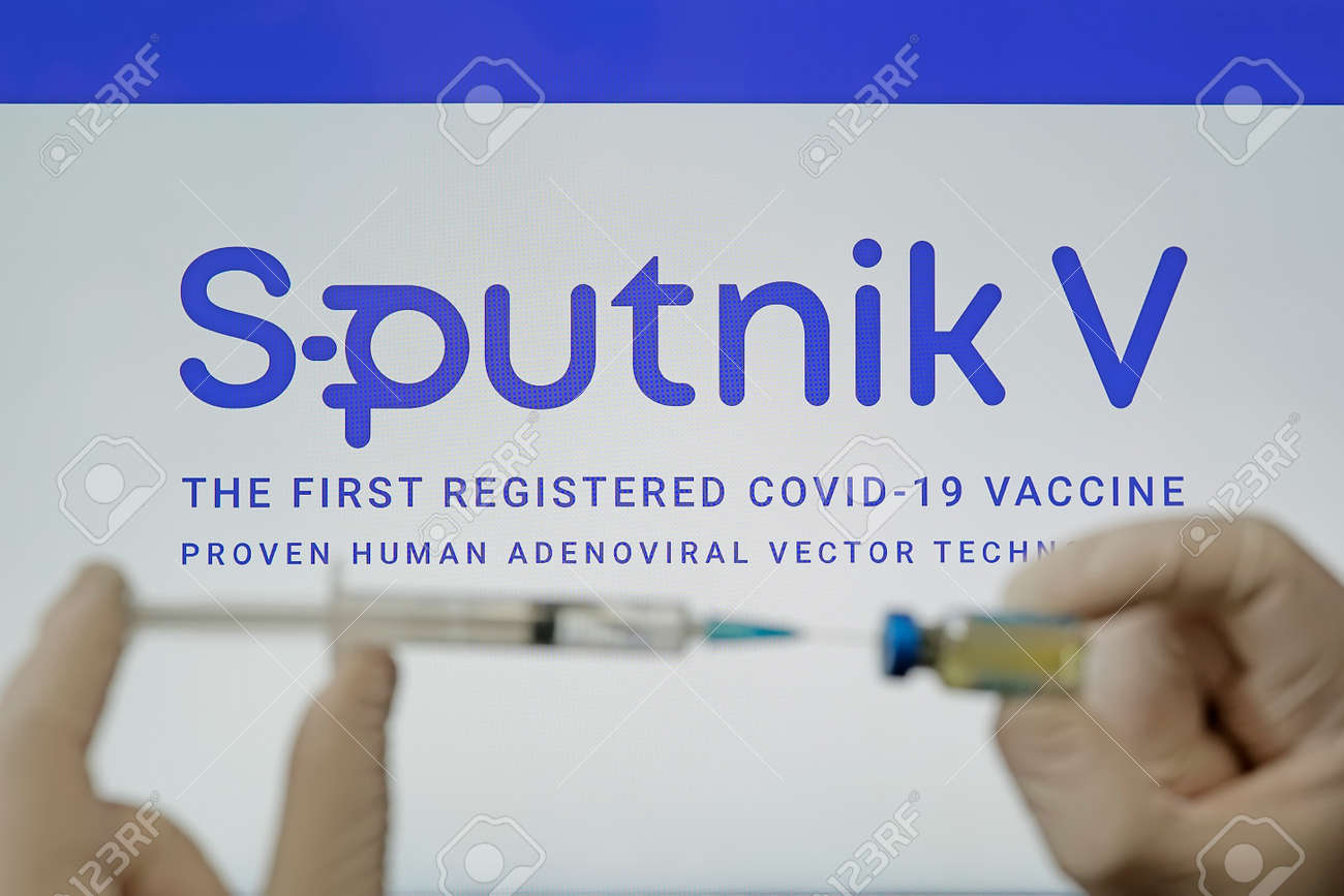 A doctor prepares a vaccine against the coronavirus covid 19 on the background of the Sputnik V logo. January 18, 2021, Barnaul, Russia. - 173498329