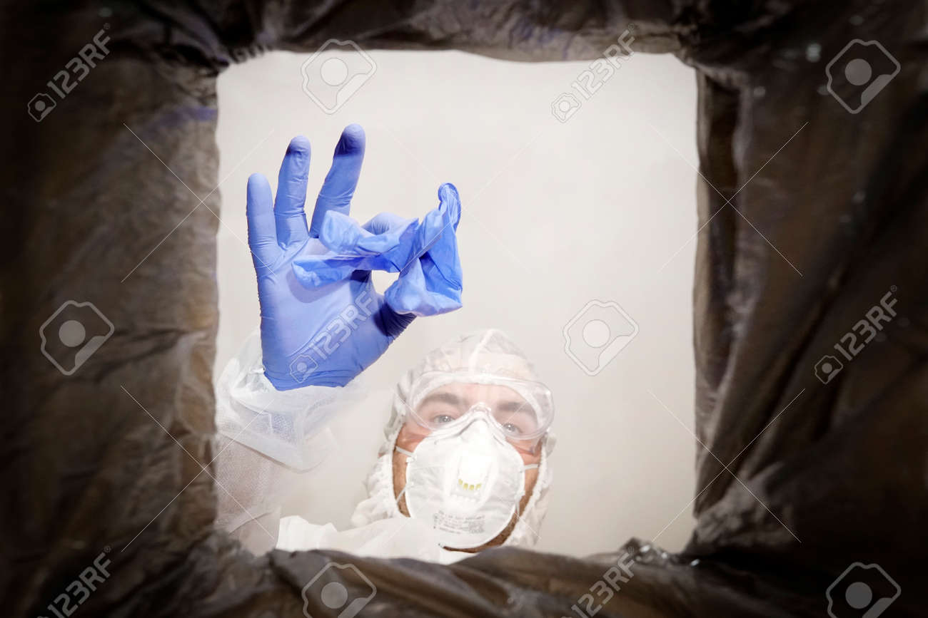man in a protective suit throws used medical glove into a trash can. Bottom view from the trash can. The problem of recycling and pollution of the planet with garbage. - 173226999